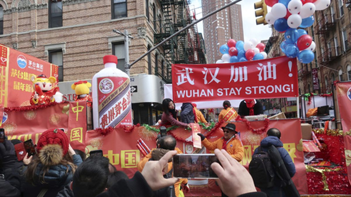 People display signs in support of Wuhan, China, at the center of the coronavirus outbreak,...