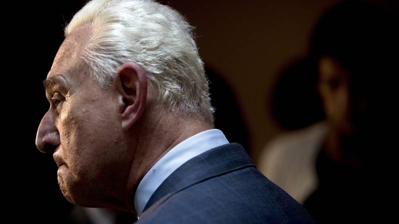 Longtime Donald Trump associate Roger Stone pauses while speaking to members of the media after...