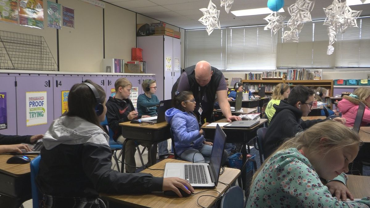 Teacher Chris Luttrell helps a student in his 5th grade class at Perrine Elementary. (Source: KMVT)
