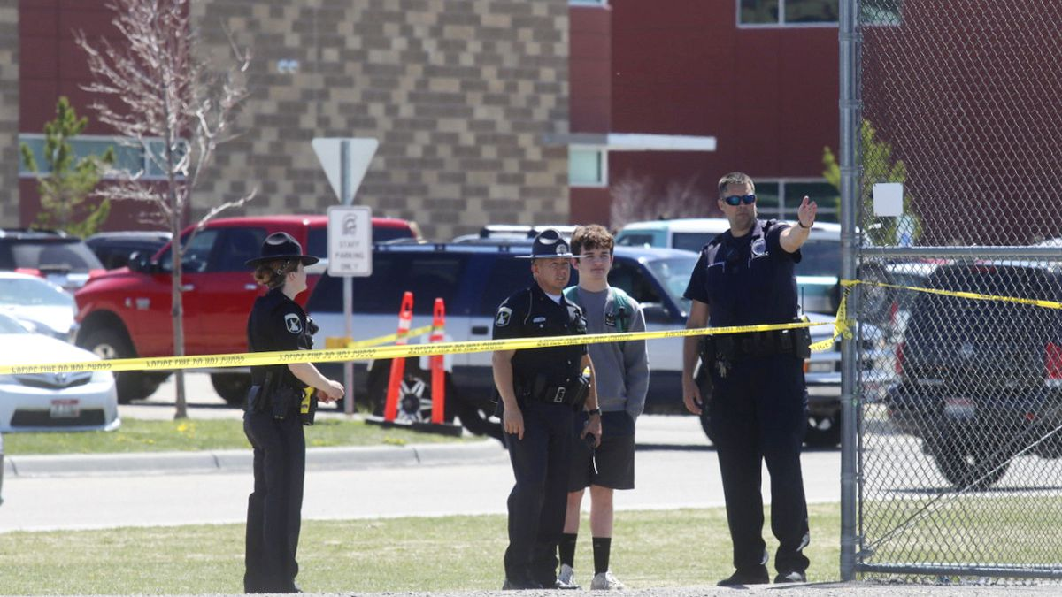 Police stand with a youth outside Rigby Middle School following a shooting there earlier...