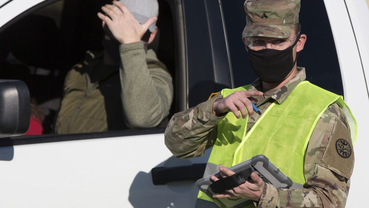 Nickolas Orr of the Idaho National Guard checks in a patient for an outdoor COVID-19 test at...