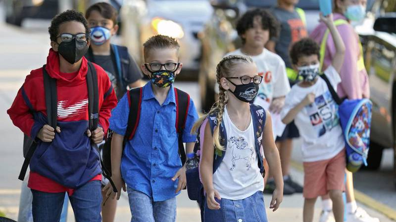 FILE - In this Tuesday, Aug. 10, 2021, file photo, students, some wearing protective masks,...