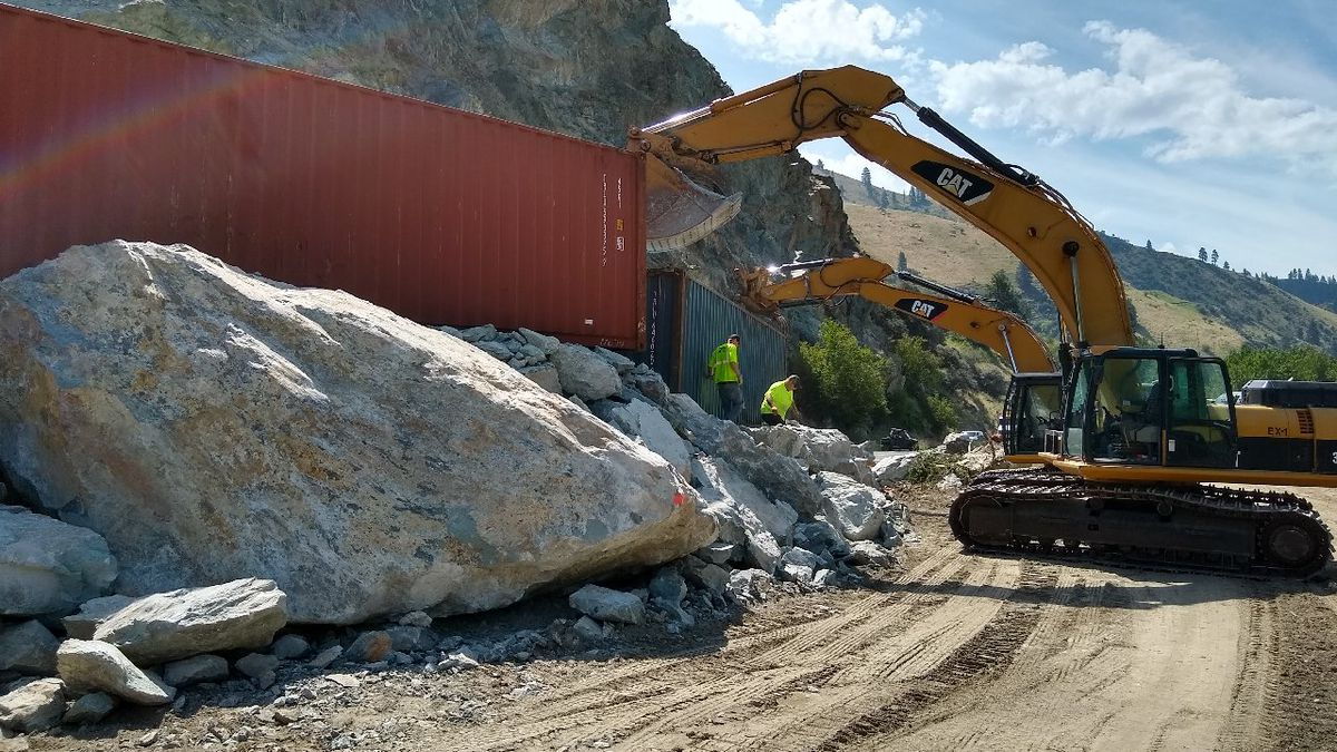 Operators fill containers boxes with rocks last week following a rockslide on U.S. Highway 95...