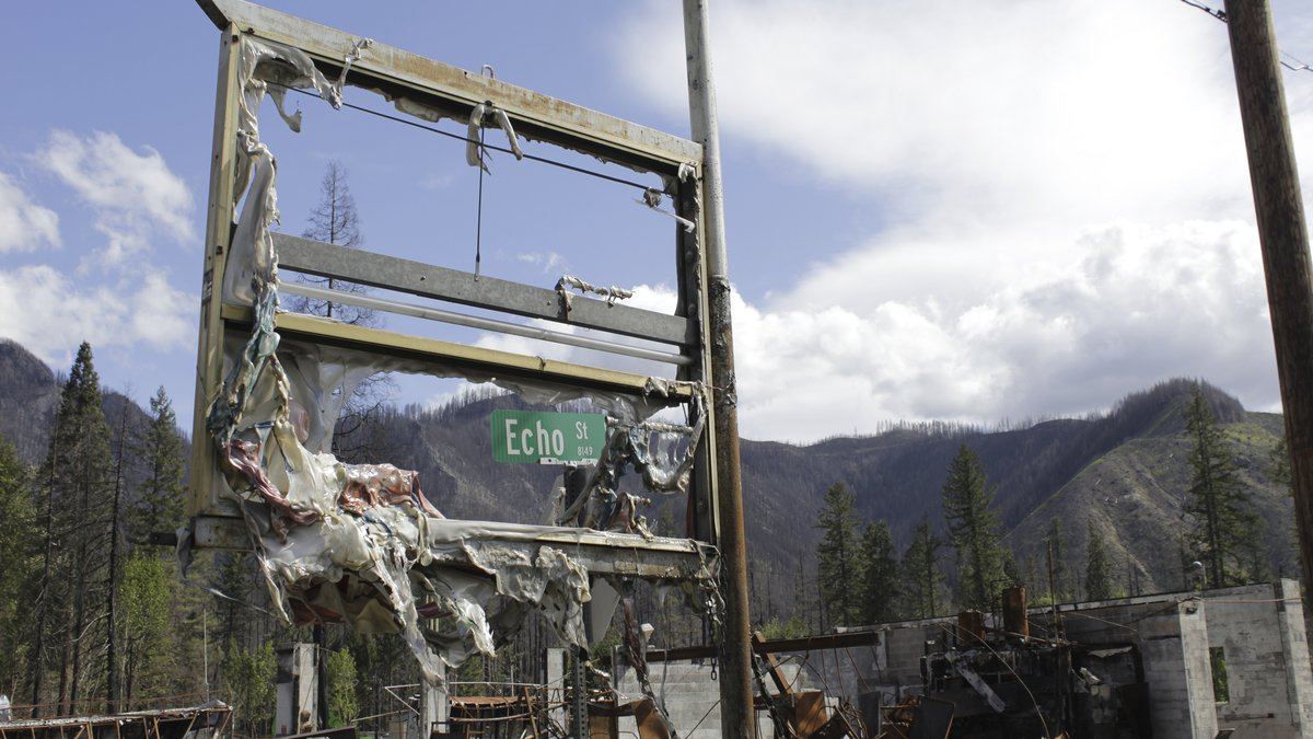 A road sign is seen through a melted gas station placard in Blue River, Ore., on May 17, 2021....