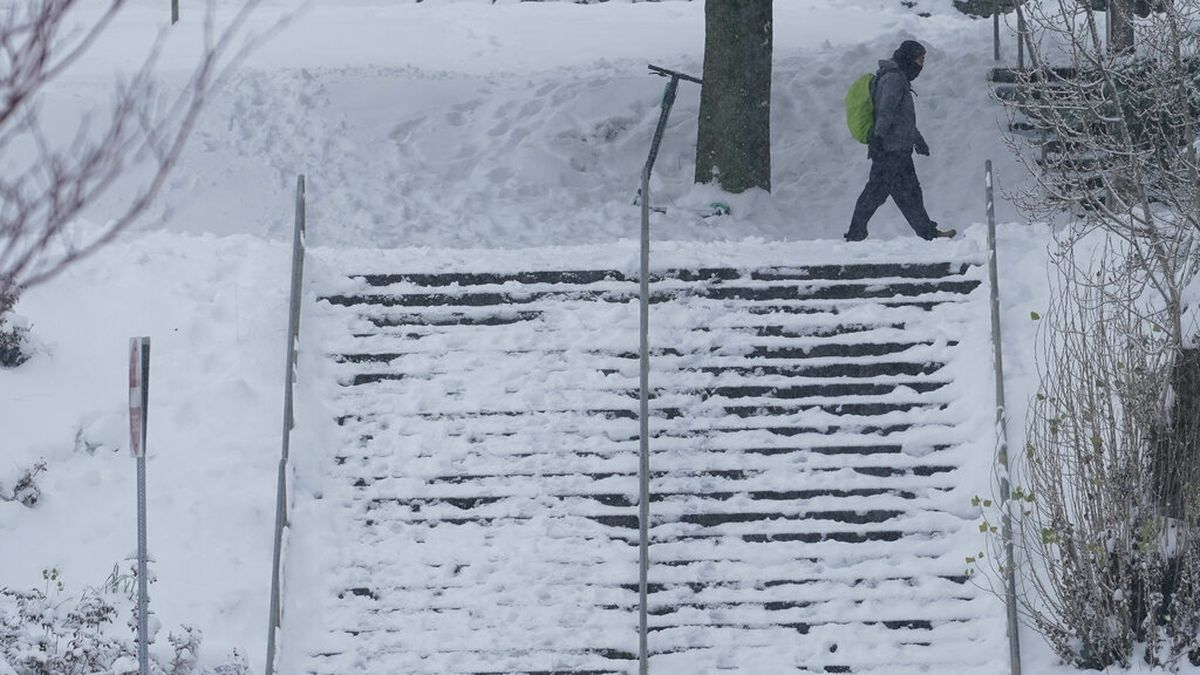 A pedestrian walks near a snow-covered staircase, Saturday, Feb. 13, 2021, on the University of...