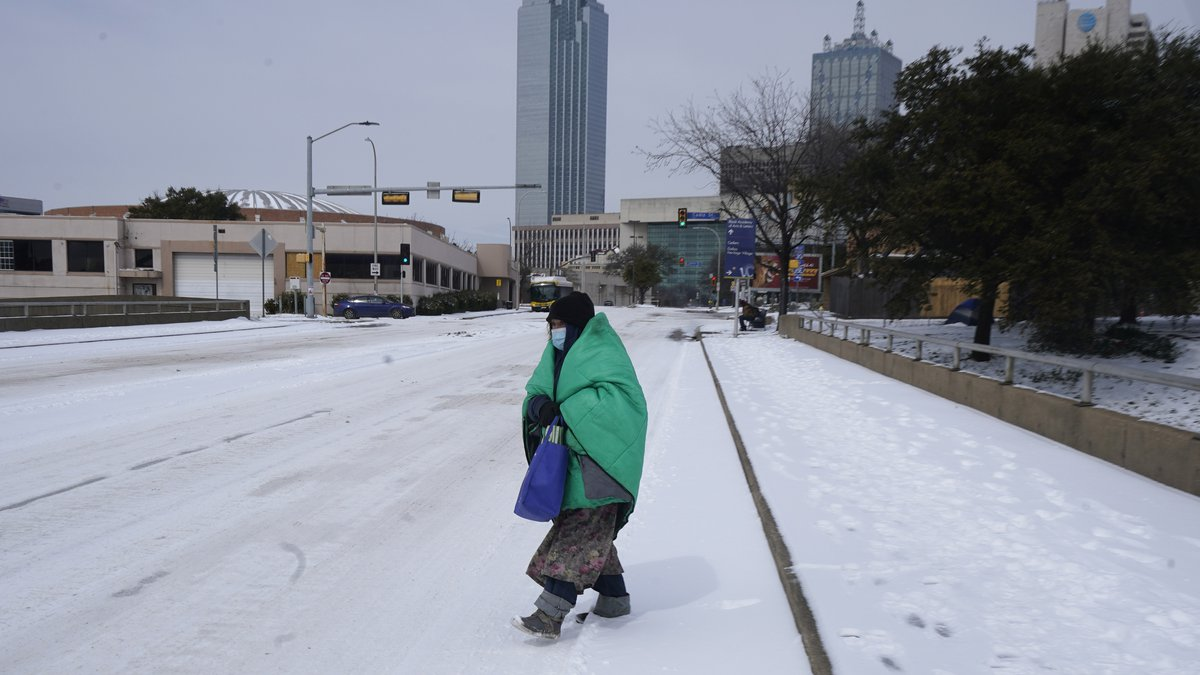 FILE - In this Feb. 16, 2021 file photo, a woman wrapped in a blanket crosses the street near...