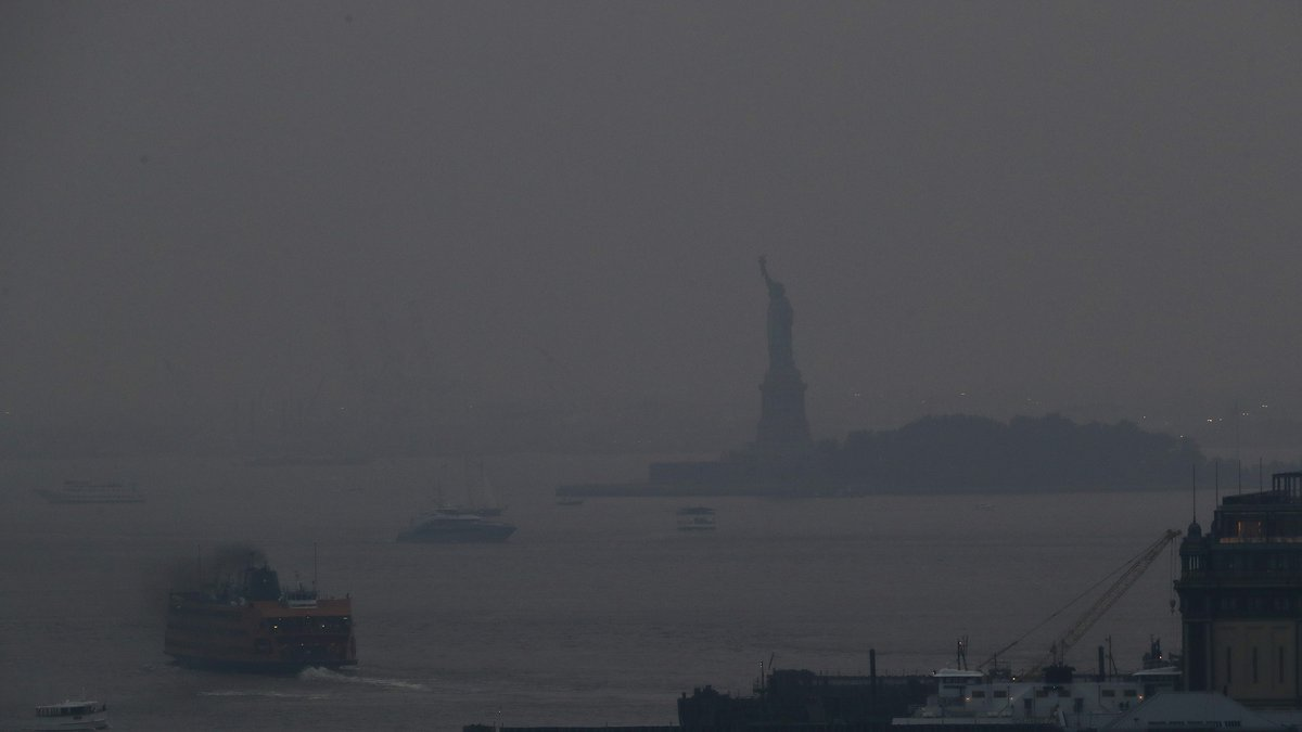 The Staten Island Ferry departs from the Manhattan terminal through a haze of smoke with the...