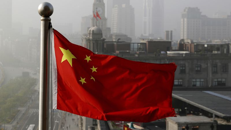 FILE - In this April 14, 2016 file photo, a Chinese national flag flutters against the office...