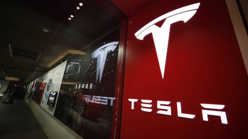 FILE - This Feb. 9, 2019, file photo shows a sign bearing the company logo outside a Tesla...