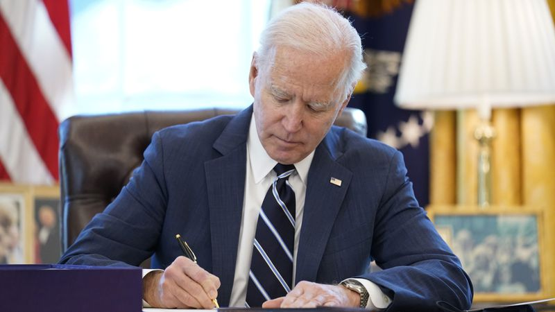 President Joe Biden signs the American Rescue Plan, a coronavirus relief package, in the Oval...