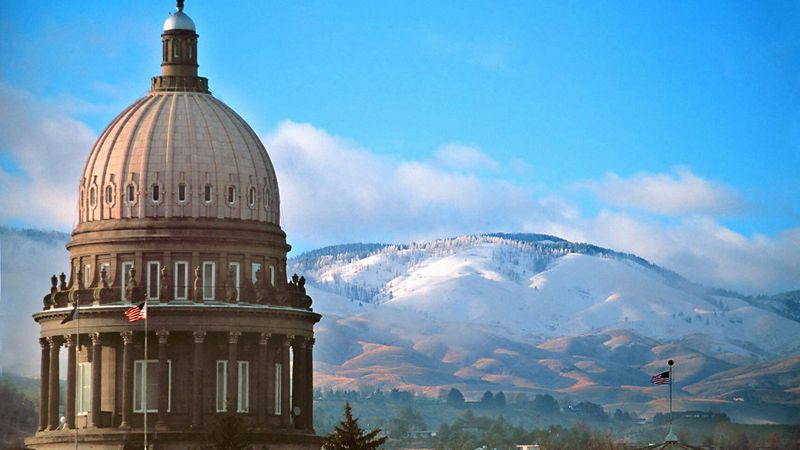 The dome of the Idaho Statehouse looms over the snowcovered foothills in Idaho's capitol city...