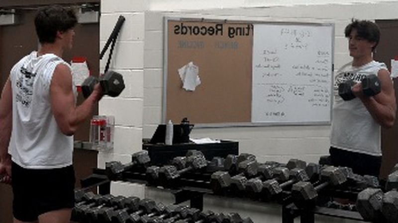 Colston Loveland is working out during weight lifting class.