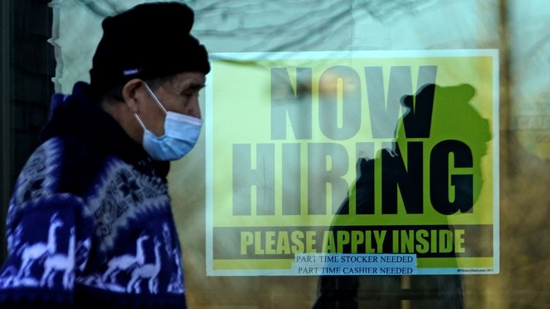 A shopper wears a face mask and he walks past a store displaying a hiring sign in Wheeling,...