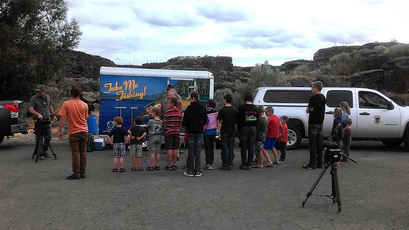 Kids line up to get their fishing poles at a recent Take Me Fishing event.