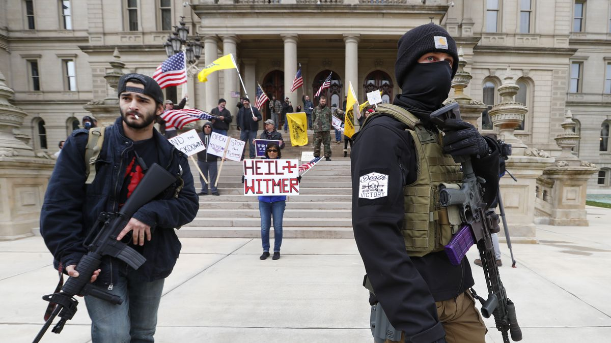 FILE - In this April 15, 2020, file photo, protesters carry rifles near the steps of the...