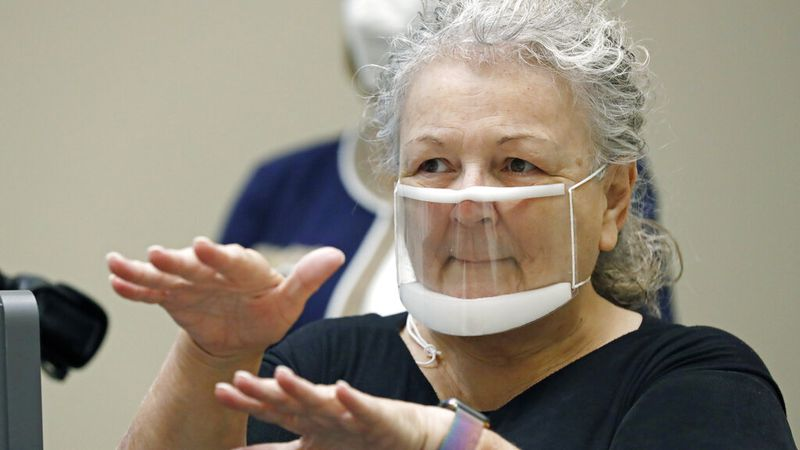 Sandra Hester, a contract sign language interpreter wears a see-thru face mask as she signs...
